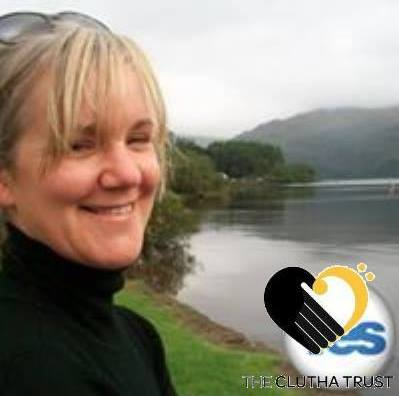 photo of Louise Malone, artist, smiling beside a lake
